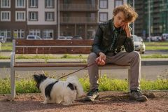 Sad lonely guy sitting on a bench with his dog. the difficulties of adolescence in communication concept. Street royalty free stock photo