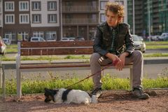 Sad lonely guy sitting on a bench with his dog. the difficulties of adolescence in communication concept. Street royalty free stock image