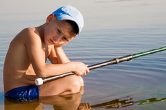 Sad and lonely kid boy sitting in the water. Kid boy sitting on the water, a sad and lonely feeling Stock Image