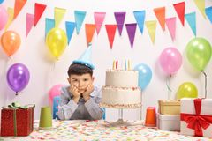 Sad and lonely little boy with a party hat. And a birthday cake Stock Photography