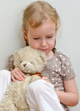 Sad lonely little girl. Sitting with teddy bear near the wall Royalty Free Stock Photos