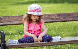 Sad lonely little girl sitting on bench. In a park, alone child in nature Stock Photos
