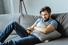 Sad lonely man holding a remote control Stock Photos