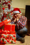 Sad lonely nerd with a bunch of Christmas gifts Royalty Free Stock Images