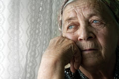 Sad lonely pensive old senior woman stock images