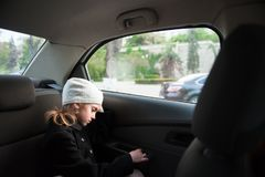 Sad lonely small girl in wool hat and coat sitting inside car near window. Sad lonely little beautiful girl in hat and coat sitting inside car near window royalty free stock photos