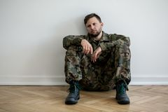 Sad and lonely soldier in green uniform with depression and war syndrome royalty free stock image