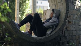 Sad lonely student in hoodie sitting alone abandoned building, puberty isolation. Stock footage stock video