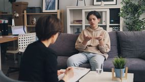 Sad teenager opening up to professional therapist in psychologist`s office. Sad lonely teenager is opening up to professional therapist in psychologist`s office stock video footage