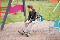 Sad lonely teenager outdoor on the Playground. the difficulties of adolescence in communication concept. Alone stock photos