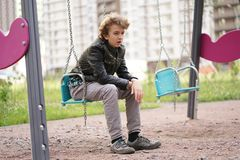 Sad lonely teenager outdoor on the Playground. the difficulties of adolescence in communication concept. Alone stock image