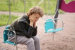 Sad lonely teenager outdoor on the Playground. the difficulties of adolescence in communication concept. Alone royalty free stock image