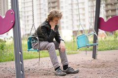 Sad lonely teenager outdoor on the Playground. the difficulties of adolescence in communication concept. Alone stock photography
