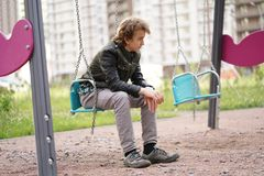 Sad lonely teenager outdoor on the Playground. the difficulties of adolescence in communication concept. Alone stock photo