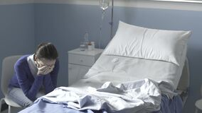 Sad woman crying next to an empty hospital bed