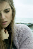Sad lonely woman feeling desperate in winter. Unhappy beautiful woman griefing in front of the ocean Stock Image