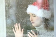 Sad woman looking through a window in christmas royalty free stock images