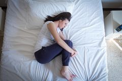Sad woman lying in the bed in fetal position. Sad lonely woman lying in the bed in fetal position royalty free stock images