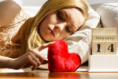 Sad woman on Valentines day. Sad lonely woman lying on bed looking at calendar, 14 Valentines day being alone with heart shape stock photography