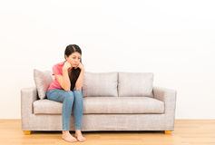 Sad lonely woman melancholy thinking about trouble. About family difficulties sitting on the sofa in the living room with wood flooring over white wall royalty free stock images