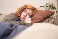Sad lonely woman. Sad lonely redhead woman resting on the sofa at home stock images