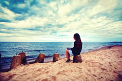 Sad, lonely woman sitting on the beach. Emotion conceptual image. Sad lonely woman sitting on the beach. Instagram vintage picture stock photography