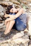 Sad lonely woman sitting on rocks Stock Image