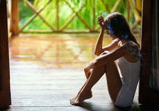 Sad lonely woman smoking cigarette and sitting on the porch duri Stock Photo