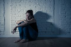 Sad lonely woman suffering from depression sitting alone and hopeless on floor at home royalty free stock photography