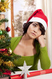 Sad lonely Xmas. A gorgeous brunette with a Santa Hat sitting dejected next to her Christmas tree with a sad expression Royalty Free Stock Photography