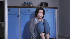 Sad lonely young Asian girl sitting on the floor in kitchen, holding her knees with arms, domestic violence concept 50