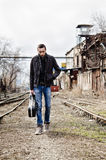 Sad lonely young man with guitar case in hand going by rails Royalty Free Stock Images
