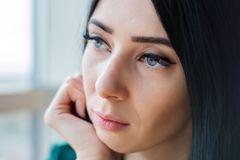 Sad lonely young woman with dark hair sits and looks out the window stock photography