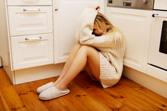 Sad lonely young woman sitting in the kitchen. Stock Photo