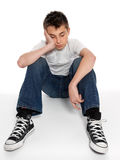 Sad, loney, depressed or listless boy sitting. A pre teen boy sitting on the floor with head in hand, bored, grief, troubled or destitute Royalty Free Stock Photo