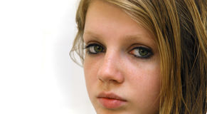 Sad look of grey teenage eyes. Teenage blond girl long-haired with sad look of grey eyes and freckles, contrasting black make-up Stock Photos