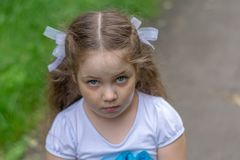 Sad look of little girl outdoor. Close up summer portrait stock photo
