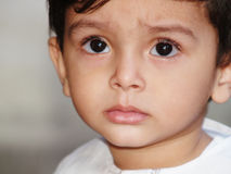 Sad-looking Asian boy. A closeup of the sad face of a young Asian boy Royalty Free Stock Image