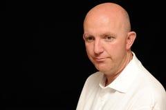 Sad looking bald man. Portrait of sad looking bald man, black background royalty free stock photography