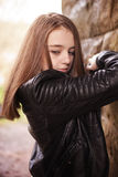 Sad looking beautiful teenage girl looking downwards. Whilst leaning on a wall Royalty Free Stock Photos