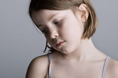 Sad Looking Child against a Grey Background Royalty Free Stock Photography