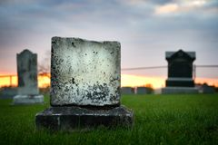 Sad grave stone evening falling. A sad looking, deteriorating grave stone shot as evening fell. It`s broken, in focus, with fungus and moss on it Royalty Free Stock Photography