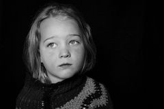 Sad looking girl. Low key Portrait of a young child. Sad looking girl Royalty Free Stock Photos
