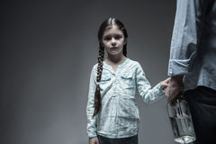 Sad looking girl touching hand of her father Stock Photo