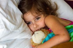 Sad Little Girl Bundled Up in Bed With a Stuffed Bear Recently R. A sad looking little girl lies bundled up, cuddling her stuffed bear, in bed. She has healing stock photos