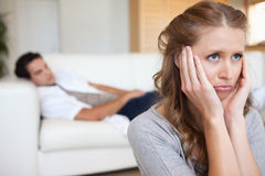 Sad looking woman with man on the couch behind her Stock Photography