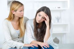 Sad looking young woman with friend Royalty Free Stock Images