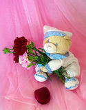 Sad love teddy bear with flowers and gifts. Stock Image