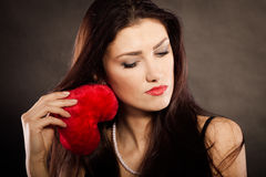 Sad lovely woman holds red heart on black Royalty Free Stock Photography