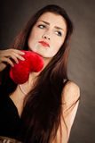Sad lovely woman holds red heart on black Stock Photography